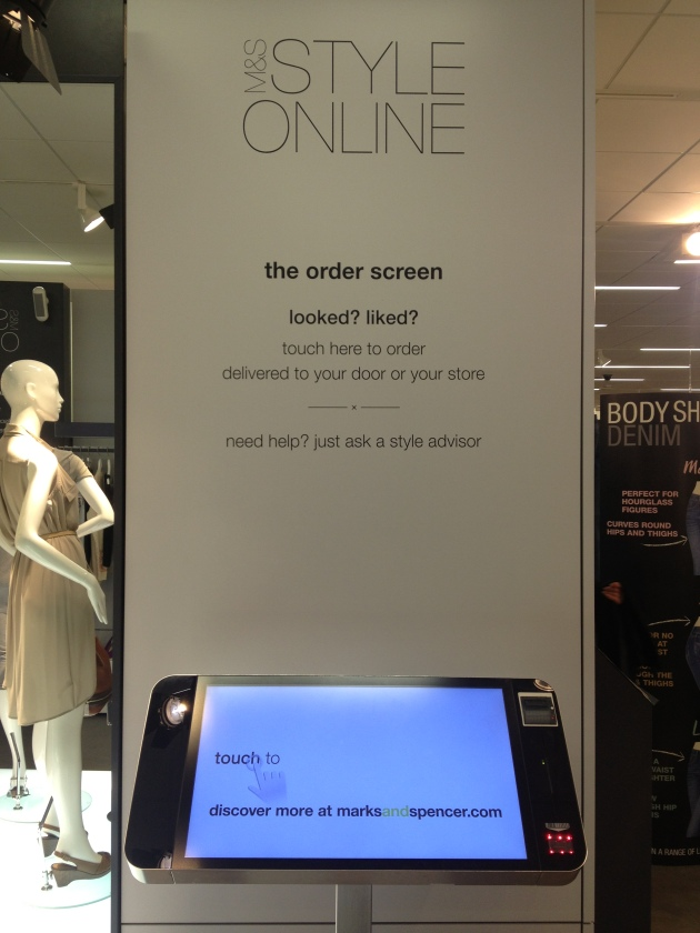 Photo of large call to action on a wall with a large tough screen device underneath.  The call to action tempts customers to search online whilst in the store.