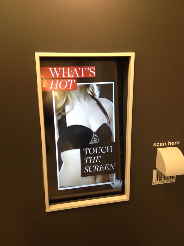 Separate touch screen built into the shop wall with a scanner next to it for scanning in items of clothing